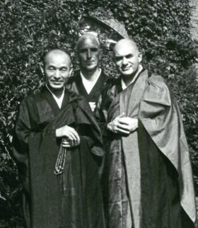 Black and white photo of three men dressed in Buddhist monk robes