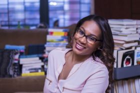 Noelle Santos sits in an office with stacks of books behind her