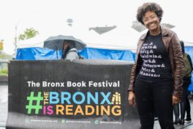 Sacaciea Fennell standing in front of banner 'The Bronx is Reading'