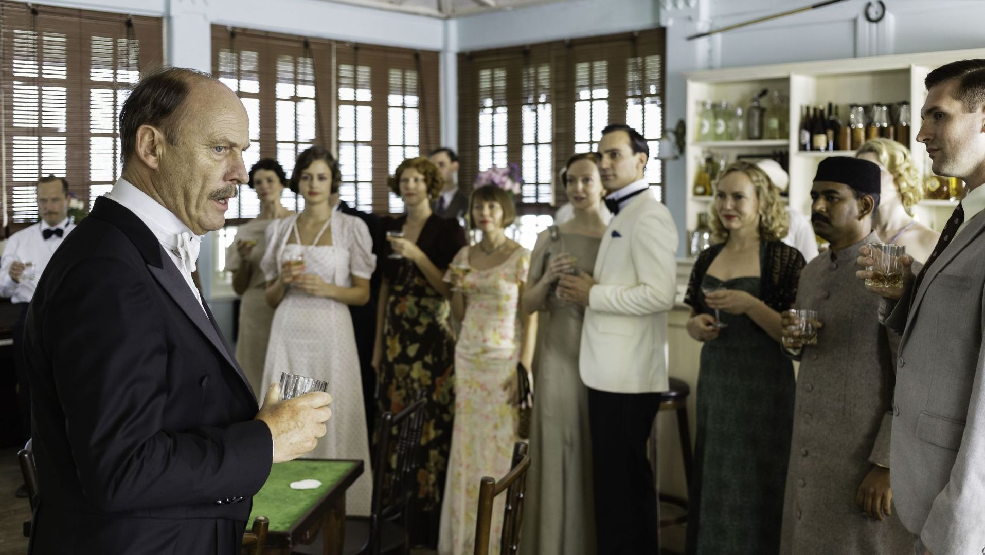 MASTERPIECE Indian Summers, Season 2 on PBS. Patrick Malahide (l) as Lord Willingdon, the Viceroy in British India. Henry Lloyd-Hughes (center in cream tuxedo jacket) plays Ralph Whelan, secretary to the Viceroy.