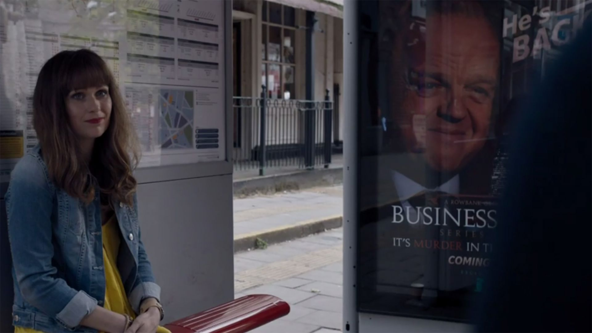 """E,"" the woman who rides the same bus as John Watson (Martin Freeman), and gives him her number in ""Sherlock: The Six Thatchers."" In the background is a poster featuring Culverton Smith, a villainous character who will be introduced in ""Sherlock: The Lying Detective"" on January 8. Image courtesy BBC/PBS."