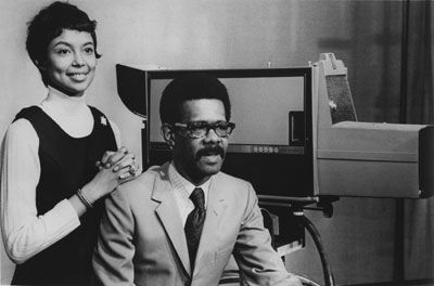 A Black woman with short hair stands next to seated Black man in a suit and tie on television set.