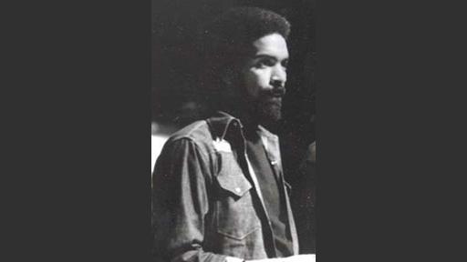 A Black man with beard seen in profile. He wears long sleeve button-down work shirt over a dark t-shirt.