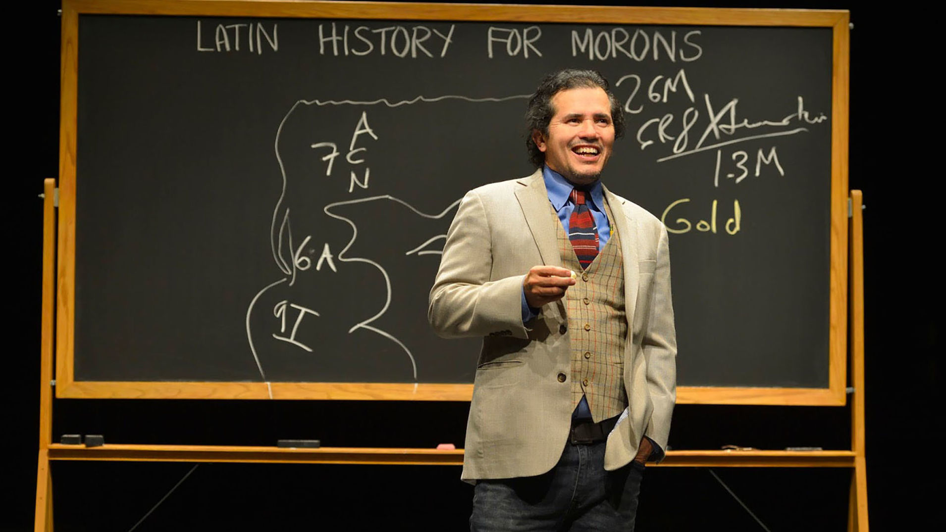 A man in light-colored three piece suit stands in front of a school chalk board and smiles.