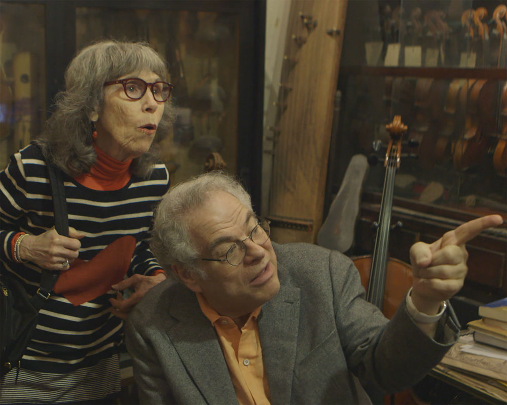 Itzhak Perlman and his wife Toby take a look at a collection of violins at a shop in Israel.