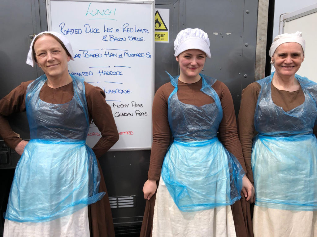 The Victoria Season 3 extras wearing bibs over their costumes during lunch on the set.