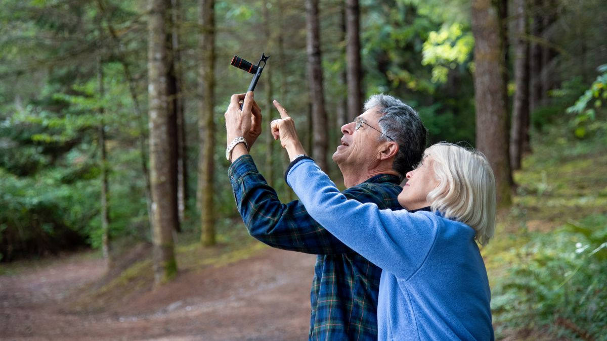 Older couple in woods, with instrument Photo courtesy Citizen Science Day.