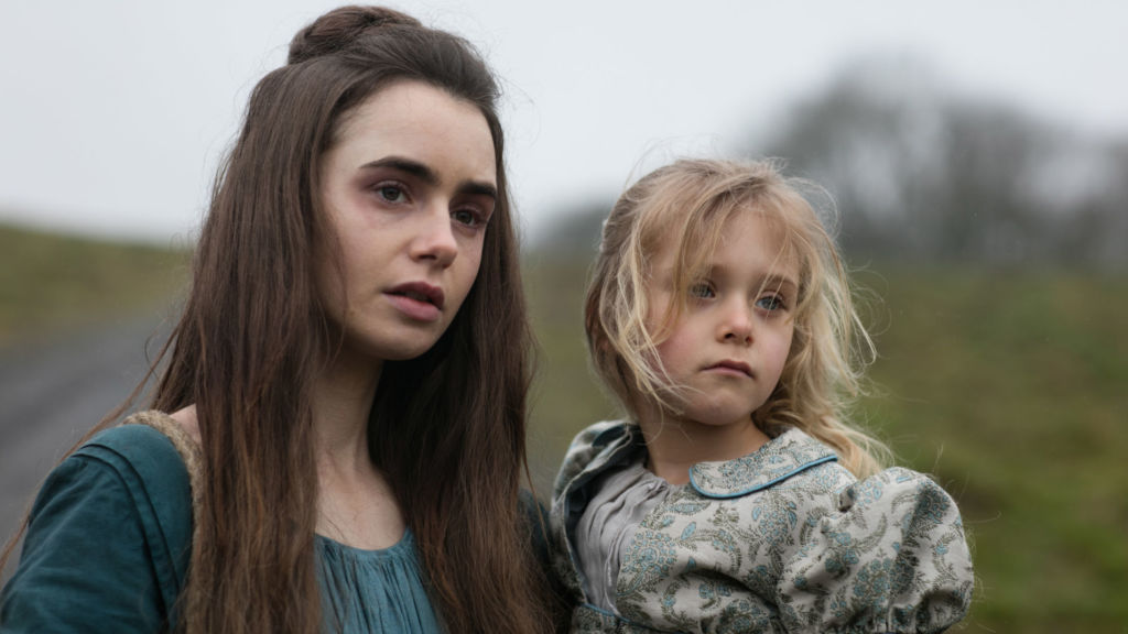 Episode Two: Fantine (LILY COLLINS) is in search of work, carrying Cosette (MAILOW DEFOY).