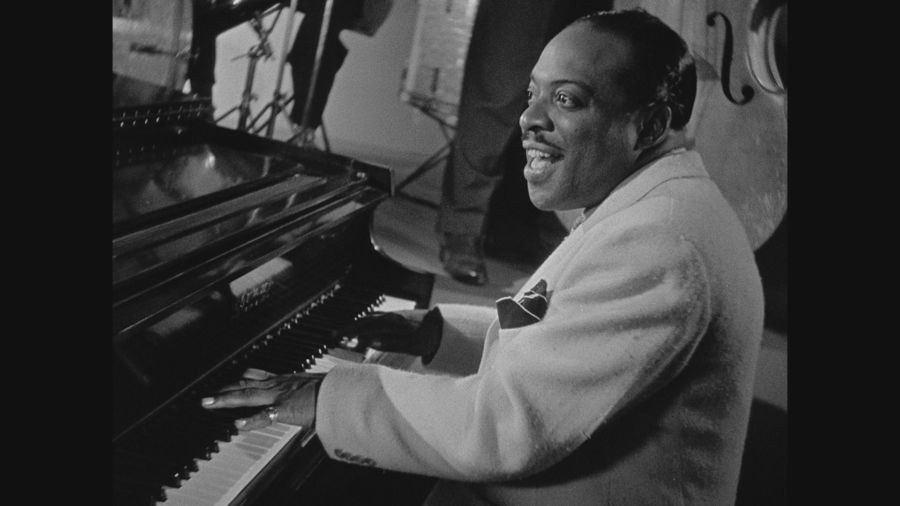 Count Basie in white tux at piano playing One O'Clock Jump