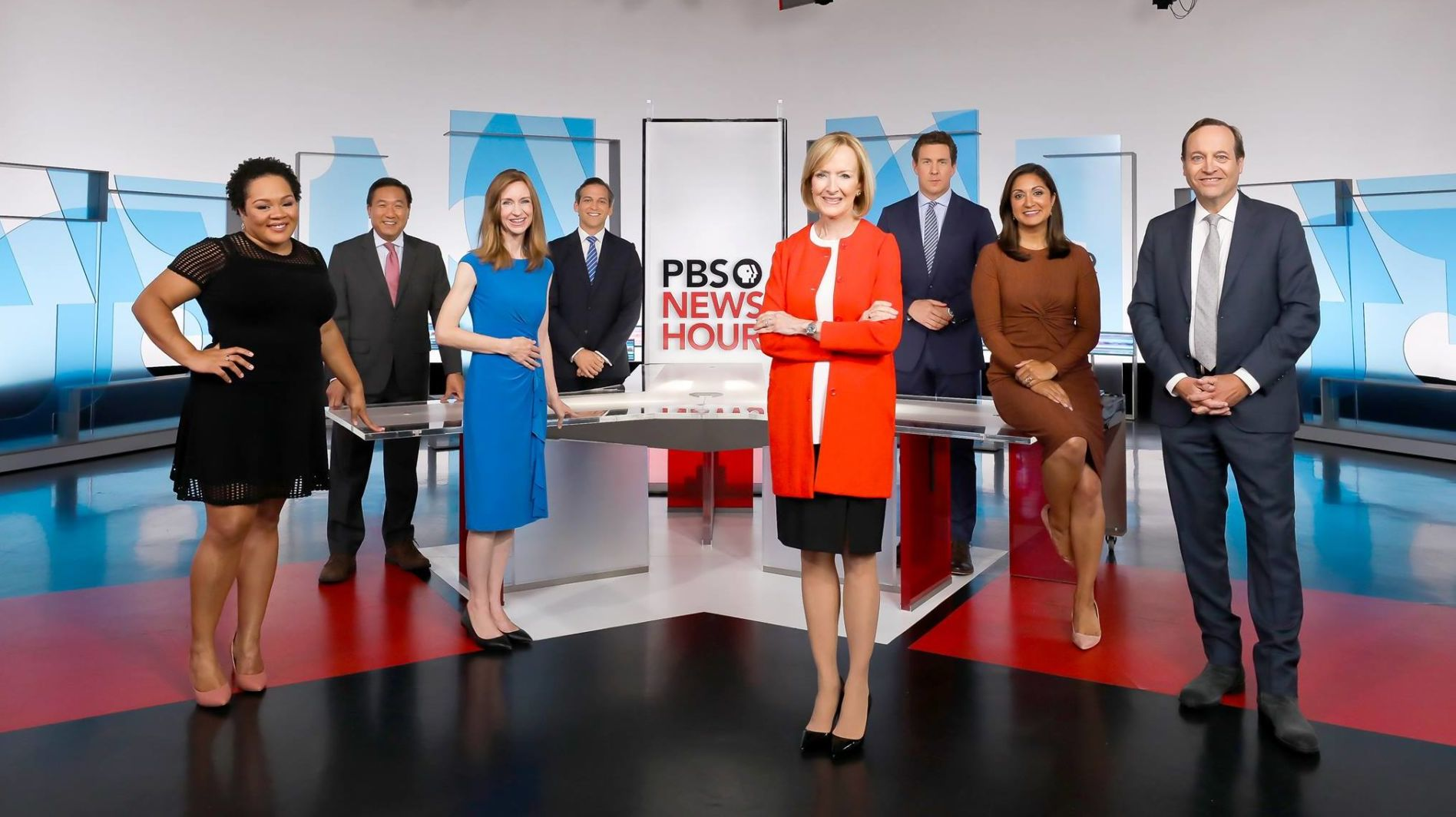 In a glossy TV studio, men and woman in business tire spread out and pose for a publicity photo. In the enter, an older woman in bright red jacket and black skirt folds her arms.