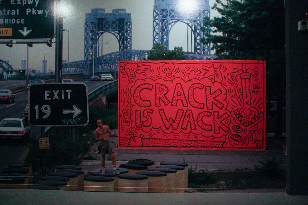 A bright orange mural with black figures on it and the words Crack is Wack, which stands right next to busy roadway. A bridge is in background and in foreground is the mural artist, Keith Haring who wears jean shorts and no shirt.