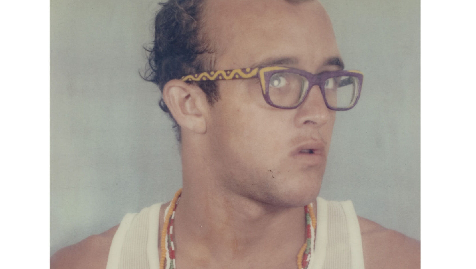 Keith Haring as adult, in a overexposed photo. He wears a white undershirt and multicolored solid-color bead necklaces. His eyeglasses have decorative pattern arm. His hair appears a bit curly and wet.