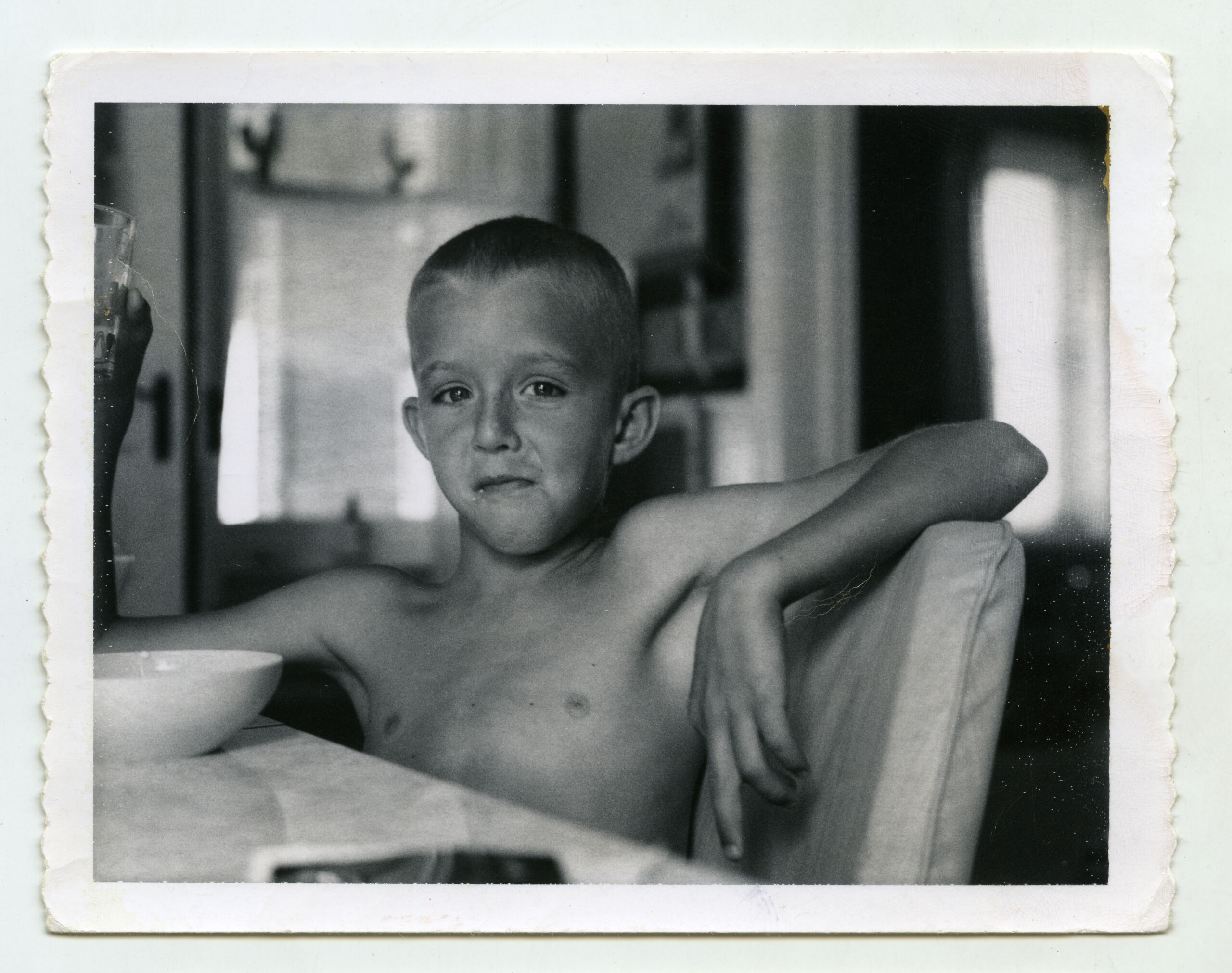 A black and white photo of a boy, perhaps 10, sitting without a shirt at a kithcen table. He smiles slightly without showing his teeh and holds a glass of water up in one hand and drapes the other arm over his chair back. A bowl is on table in front of him.