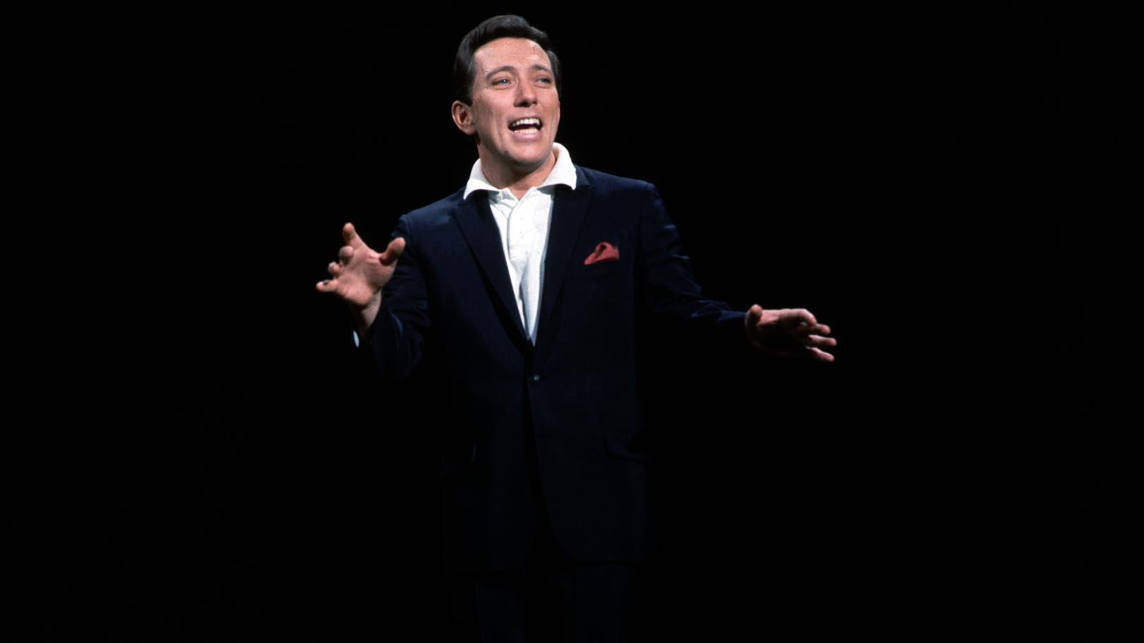 A man in black jacket and white shirt spreads his arms as he sings. The entire background is black.