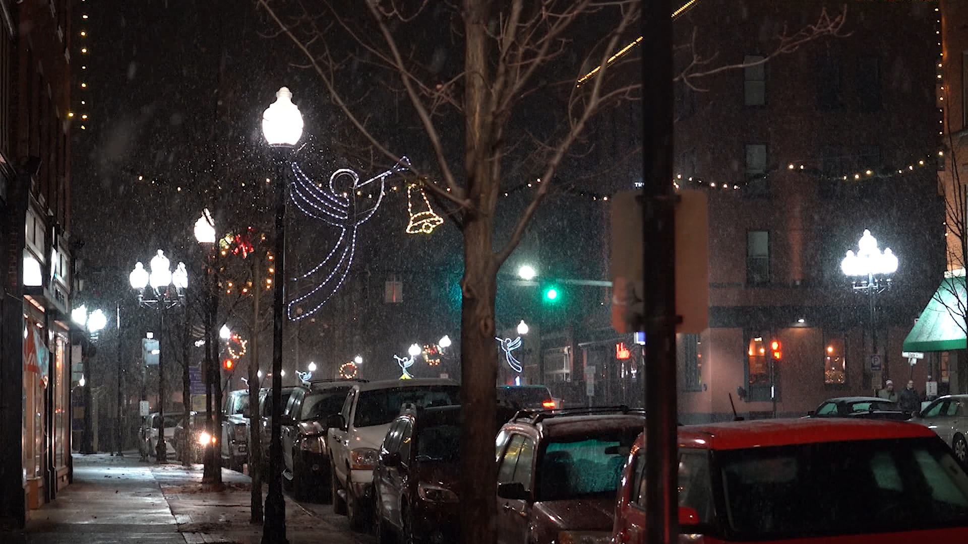Nighttime on town street, lined with parked cars and Christmas lights.