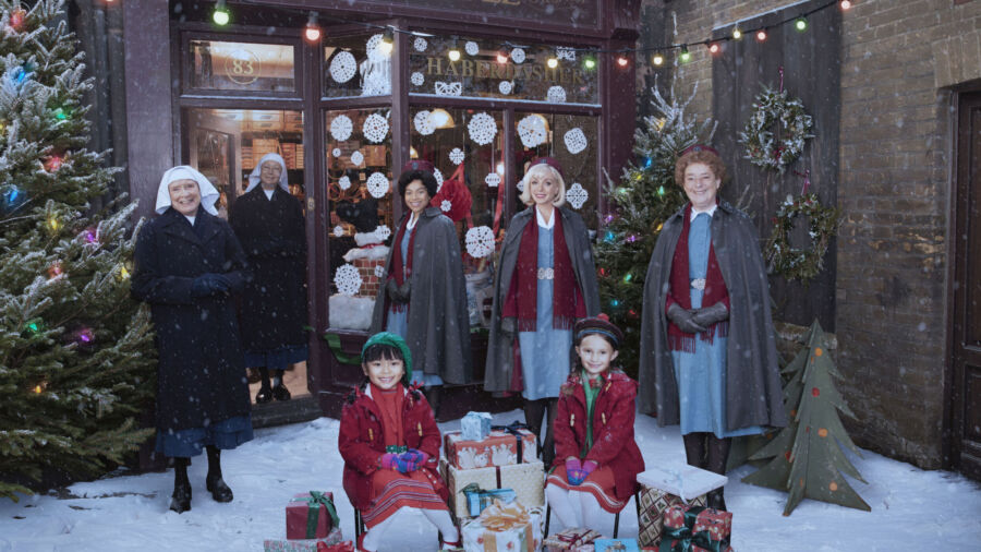Nuns, nurses and children pose in front of a store window, next to Christmas tree