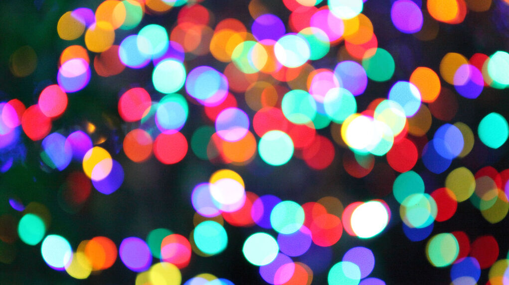 A soft focus, blurry shot of colored Christmas lights in the dark.