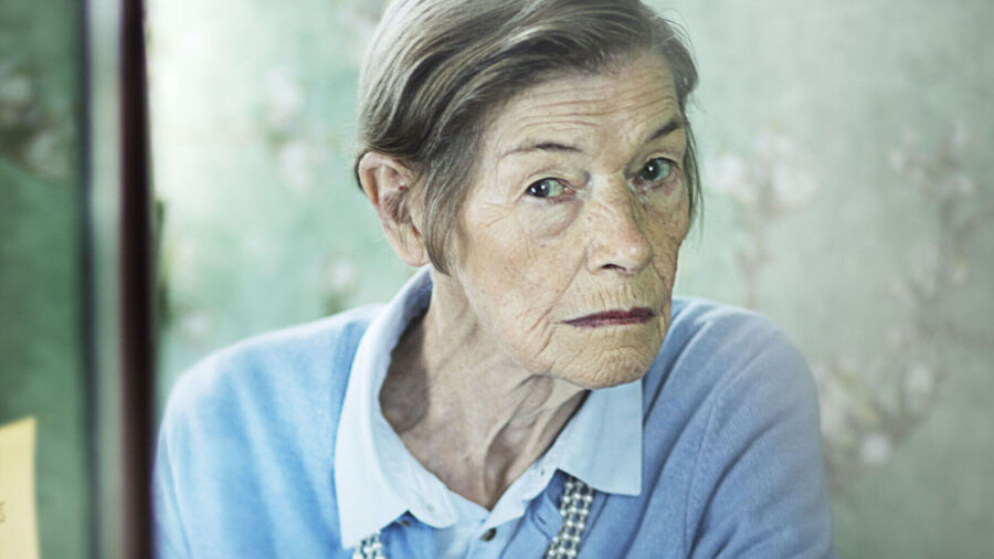 An 80-year-old woman with short grey hair wears a matching shirt and sweater with pearl necklace and looks in a dressing mirror with suspicious expression. There is a black and white photo of a young woman on the mirror's eddge.