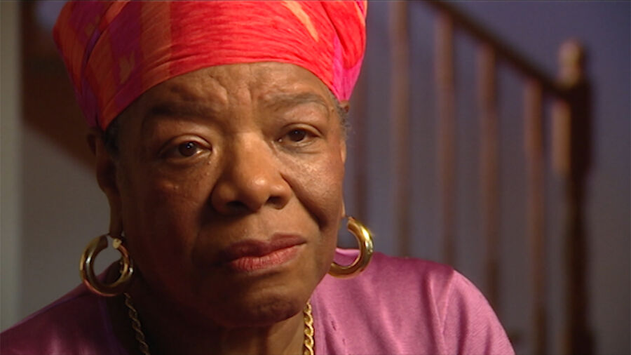 A black woman wears bright red headscarf, gold loop earring and a light purple top.