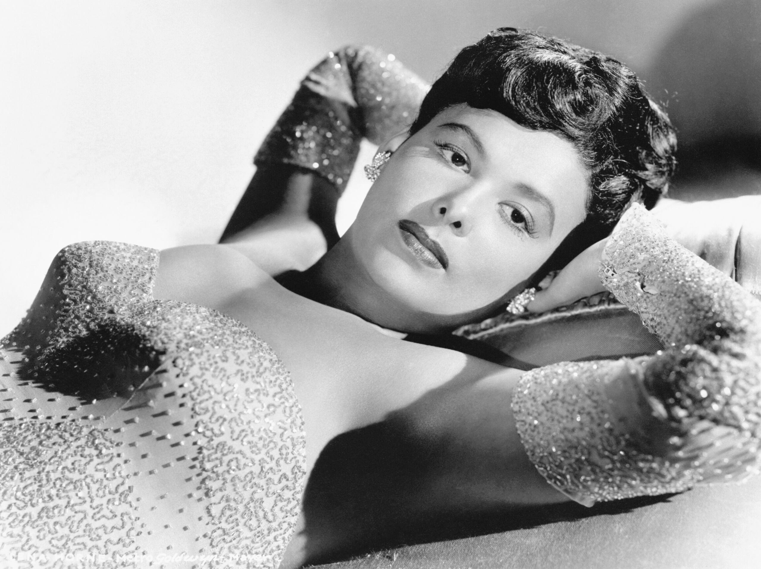A light-skinned Black woman reclines in a sequined gown with her head resting in her hands.