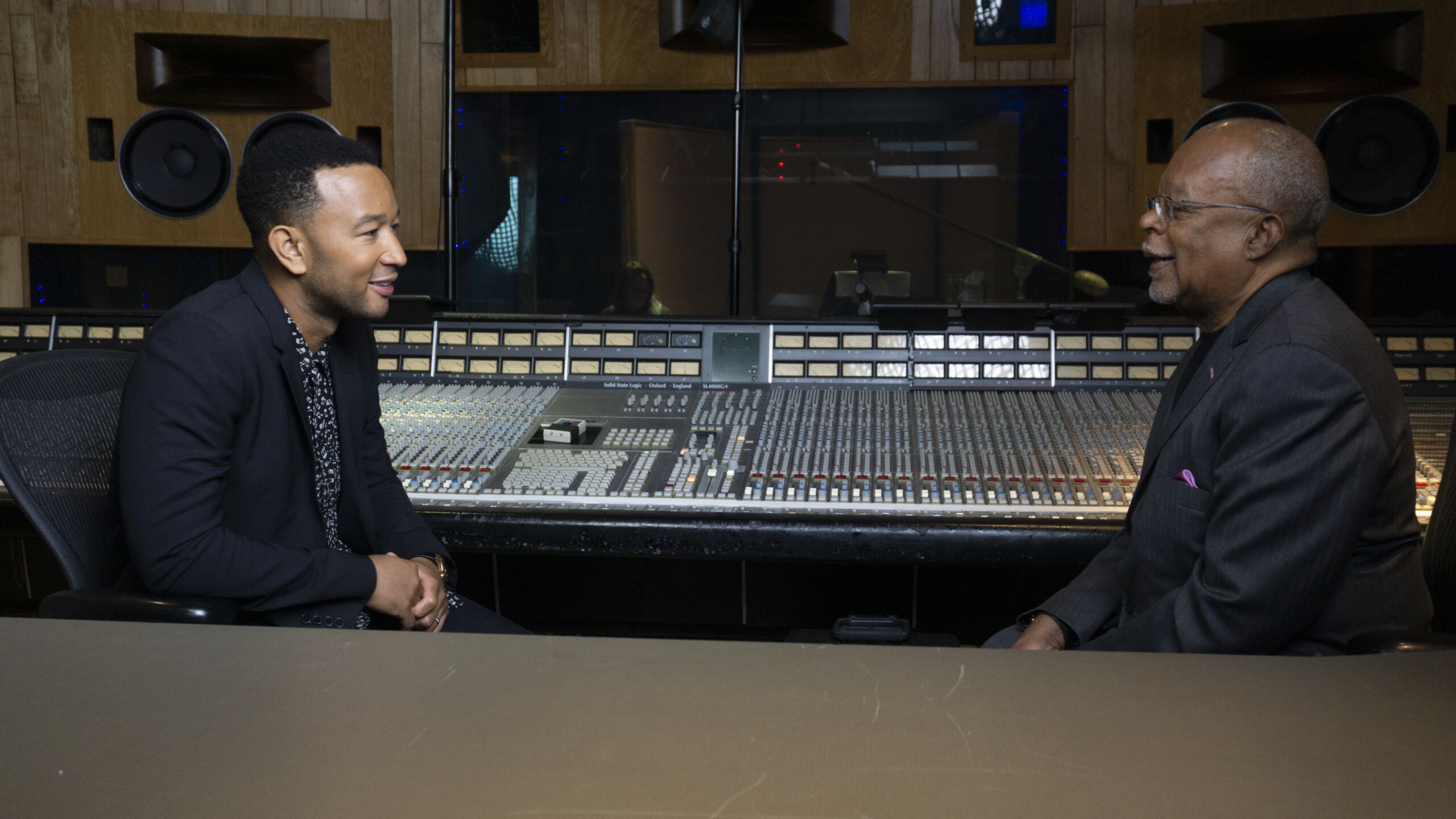 Two black men sit at a distance facing each other; a music studio mixing board runs between them.