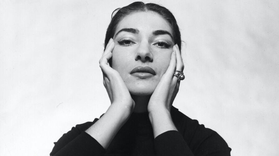 woman in black sweater hold her face in her hands. She has dark hair parted in middle and pulled close to head. She gazes at camera and doesn't smile.