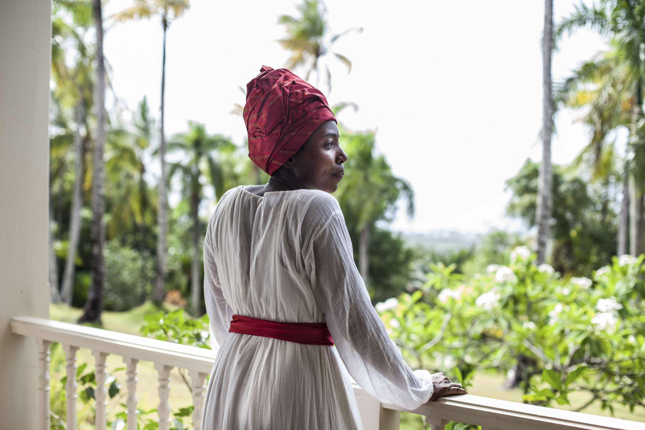A Black woman in red cloth headwrap and white dress with red belt stands at a wooden balcony and looks out to tropical greenery.