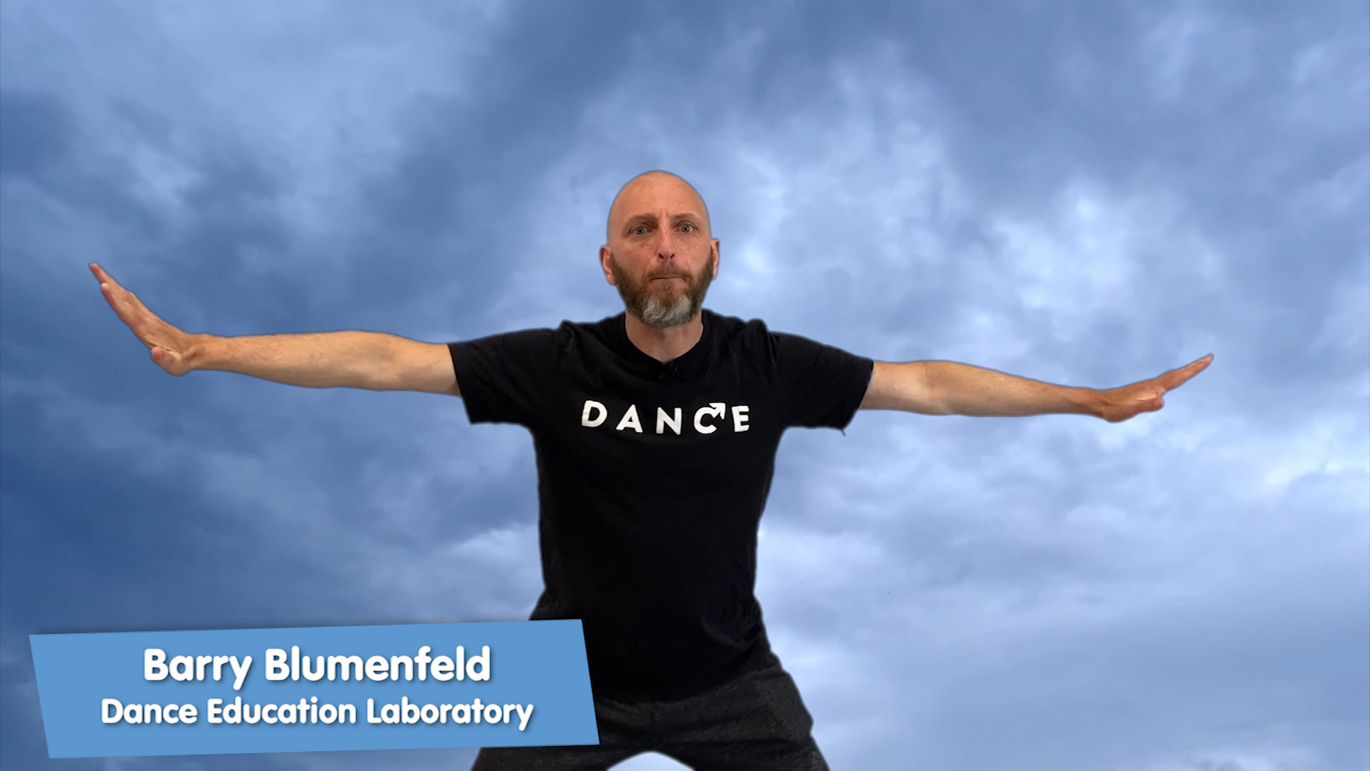 A thin bald man with a beard wears a black t-shirt that says DANCE and holds his arms out like a plane. He squats a little bit.