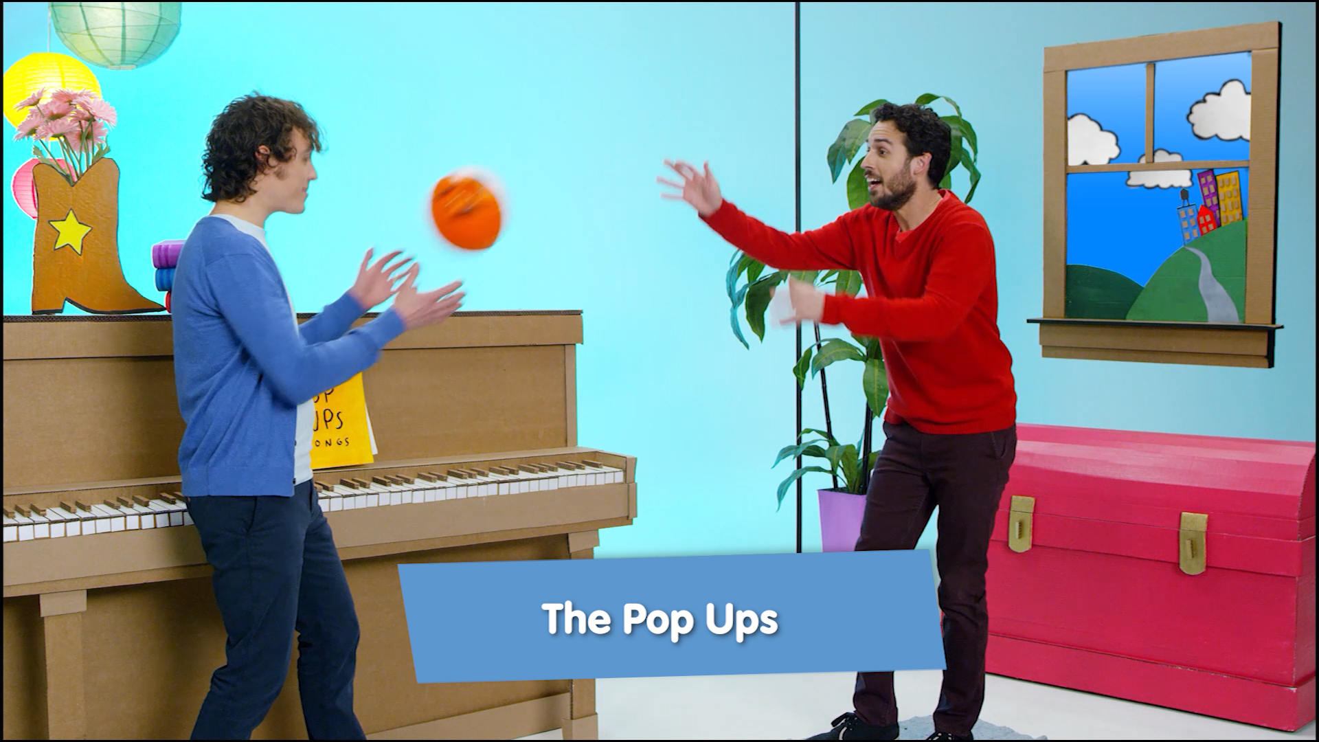 Two men are in a room with an upright piano and red floor chest. They toss a ball between them.