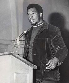 A Black man with long sideburns stands at a podium with a microphone