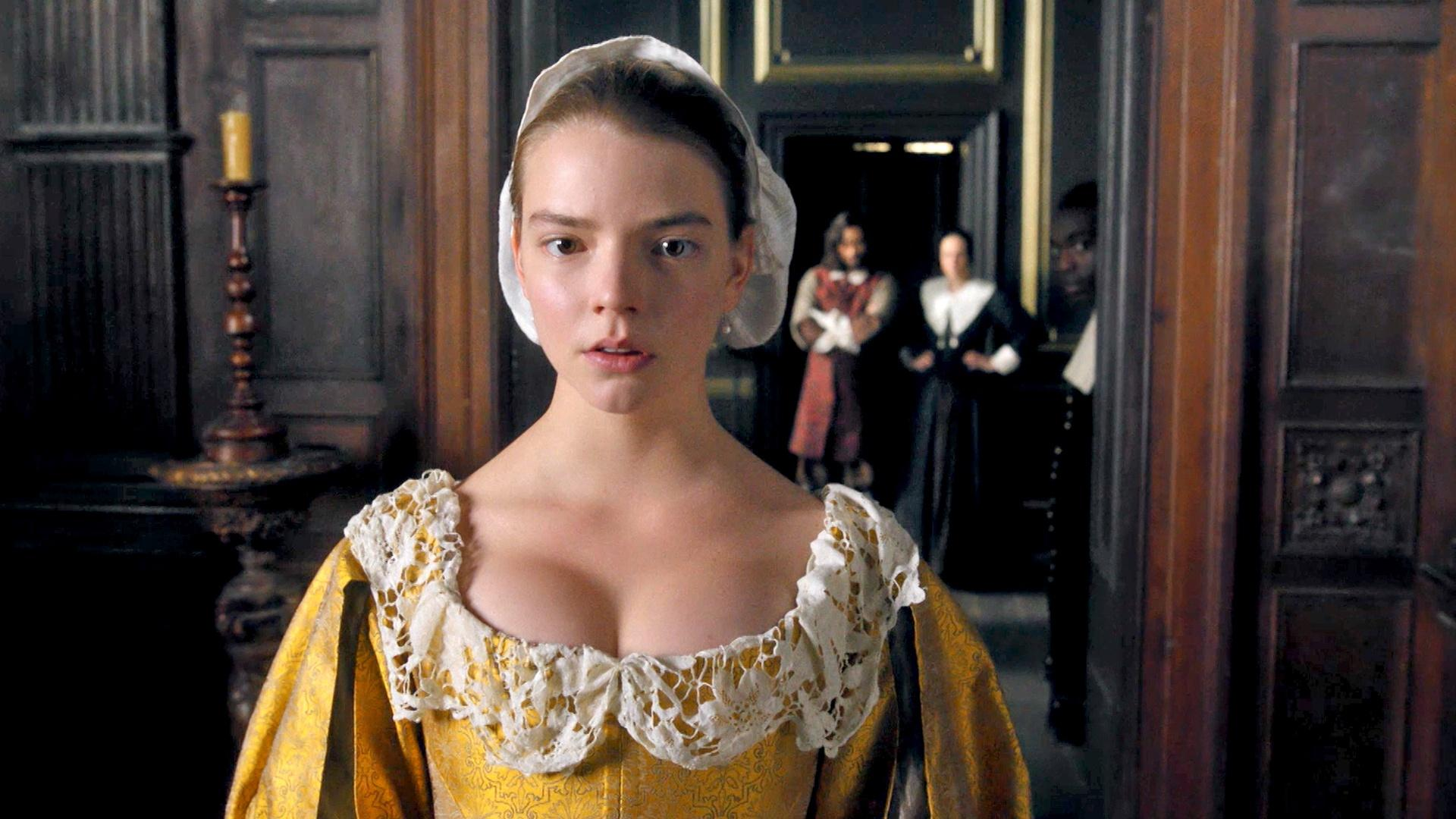 A young woman in 17th century bright yellow dress stands in a wood paneled interior. People are down the hall looking at her.