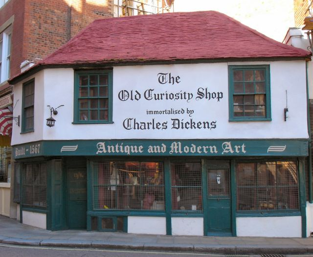 A white, two-story building with red roof and green accents sits on a street corner. Large lettering painted on the second floor says it is the Old Curiosity Shop visited by Charles Dickens.