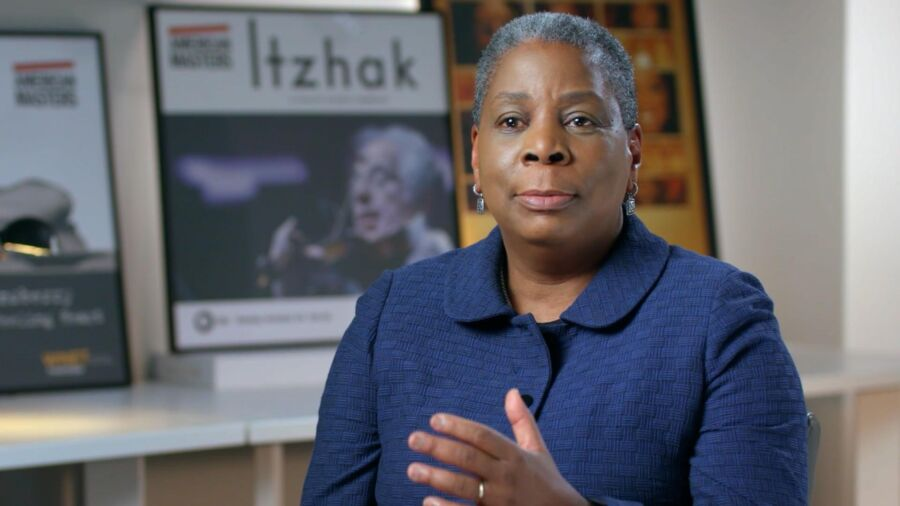 A Black woman with short greying hair and wearing a dark blue suit jacket gestures towards the camera. Behind her are documentary film posters.