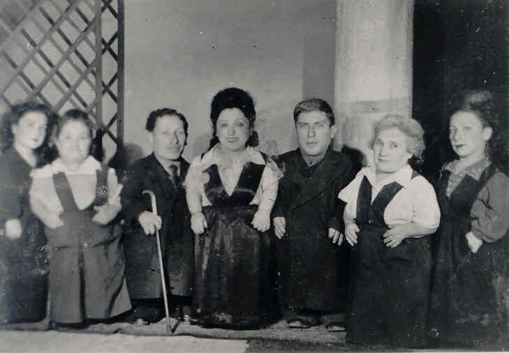 Seven dwarfs in suits and dresses pose in line for a photo.