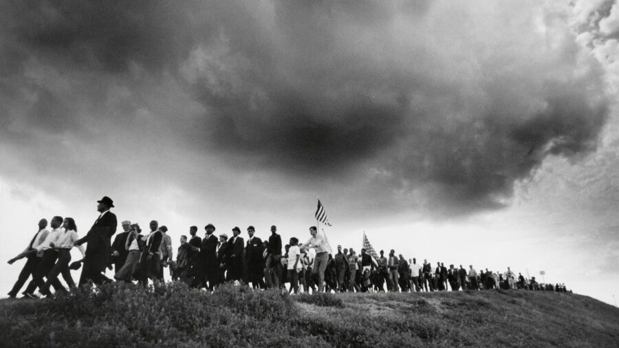 A long line of people marching, mostly in dark suits, are seen on a grassy ridge. An American flag rises in the middle of the line and heavy storm clouds are visible above the marchers.