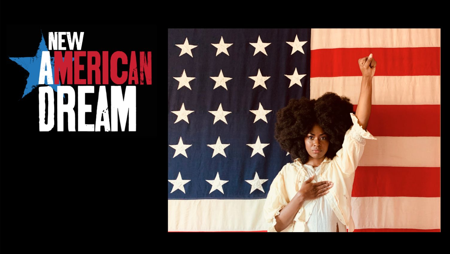 A black woman with Afro stands in front of large American flag background with her fist raised in front of an American Flag and raises her left arm and puts right hand on chest