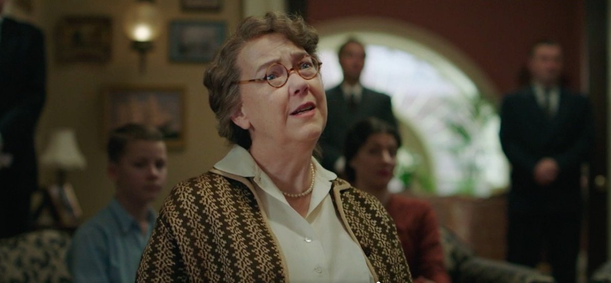 A middle age woman in blouse, knit sweater, pearls and round eyeglasses looks perplexed. Others are behind her in a room.