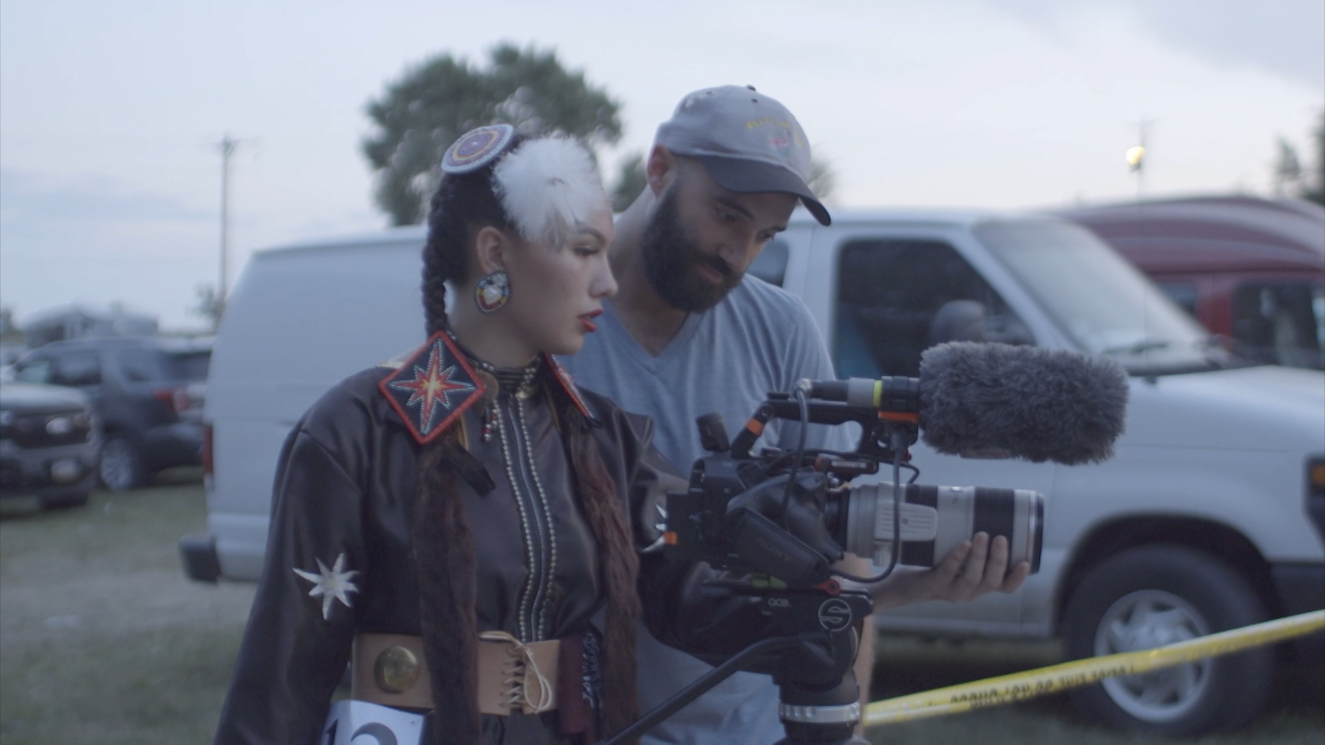 A young woman with dark braided hair and wearing Native American clothes and hair pieces looks at film camera with man with beard, cap and t-shirt.