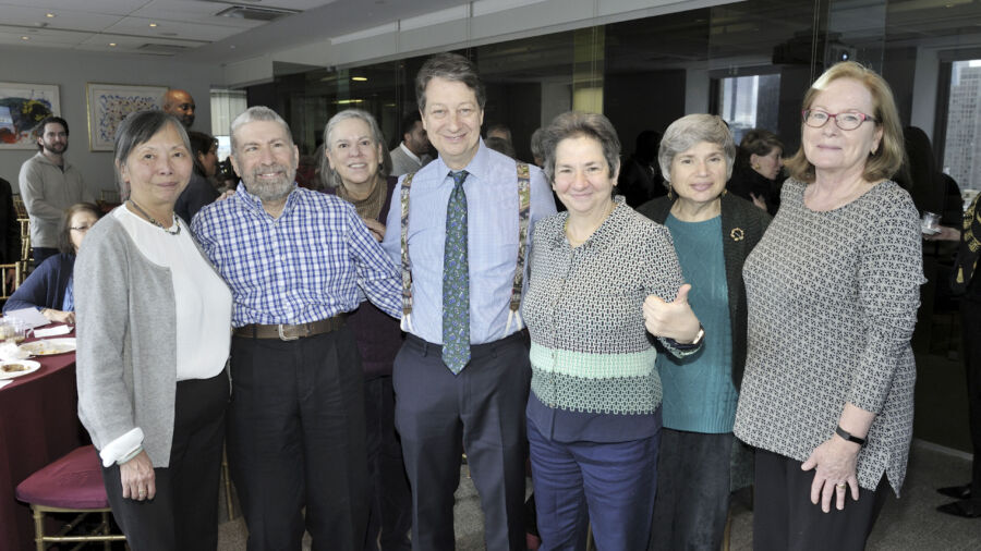 Seven older adults pose for photo in a conference room