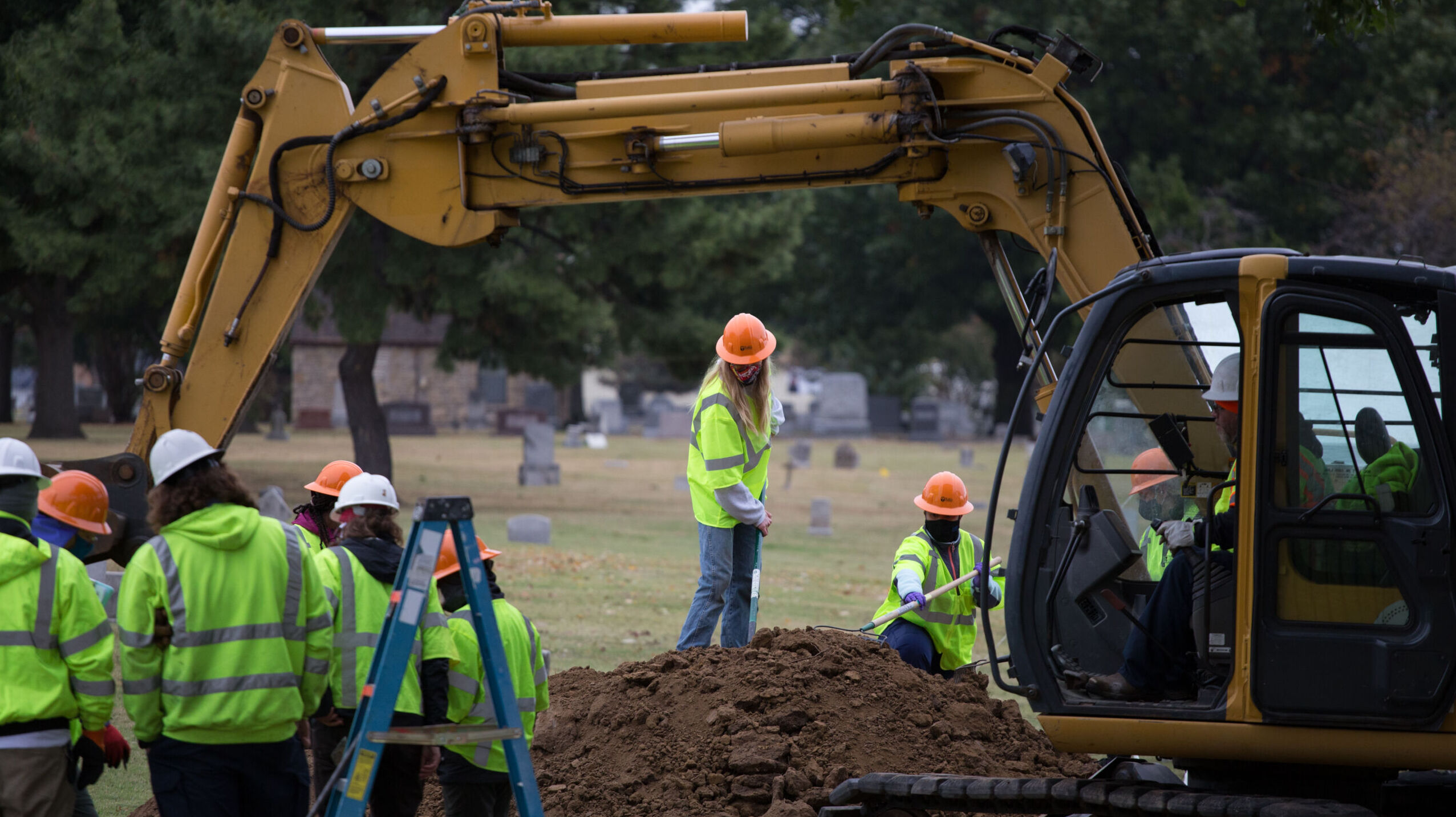 People in flourescent yellow vests and hard hats stand around a high mound of freshly dug dirt near a cemetery. A bulldozer is partially in view.