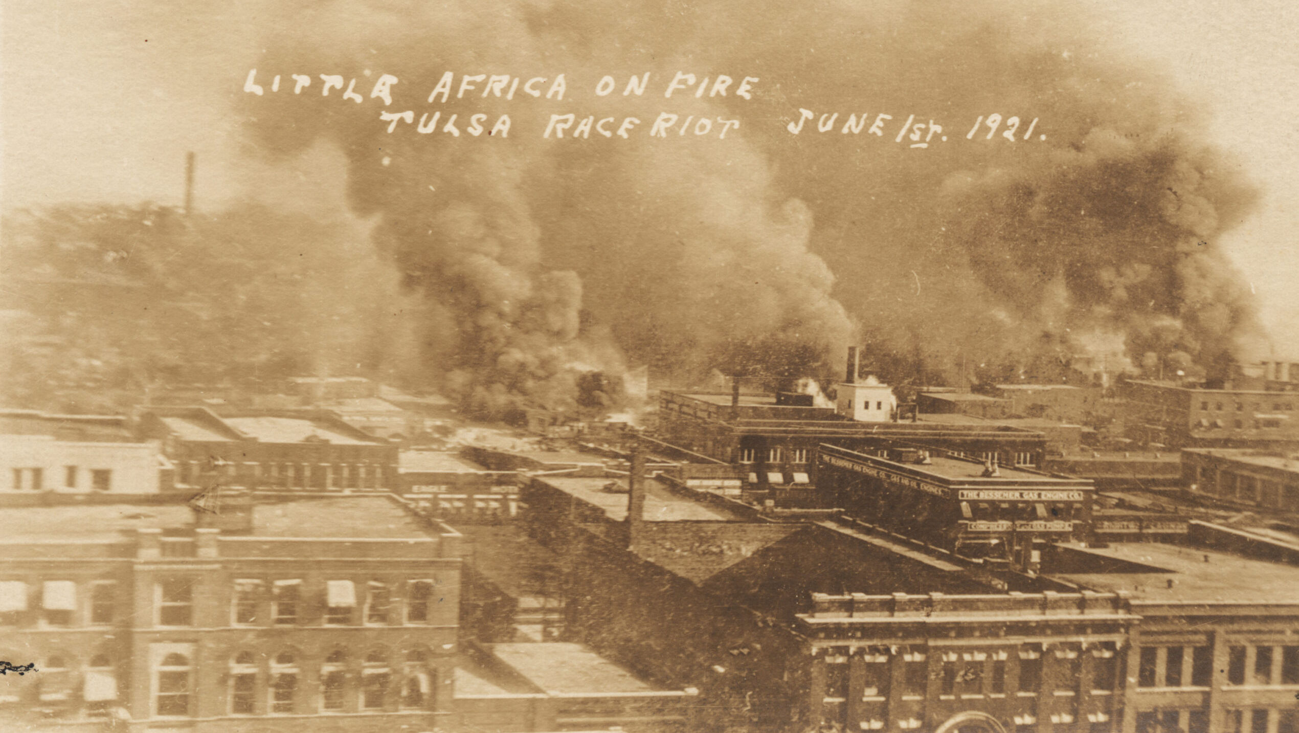A sepia tone photograph showing rooftops of brick buildings, many of which are obscured by clouds of smoke from a fire.