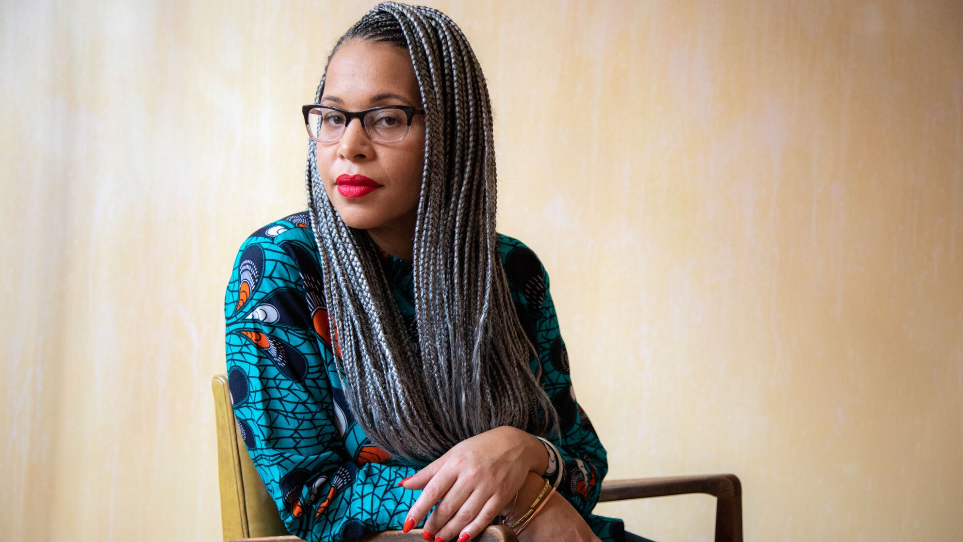 A black woman with long braid extensions sits sideways in a chair. She has glasses.
