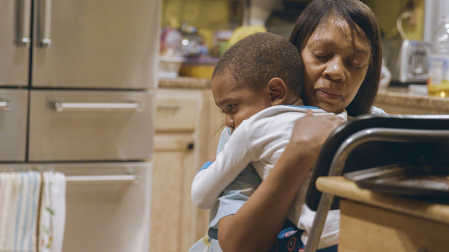 A black woman kneels to hug a small black boy in a kitchen.