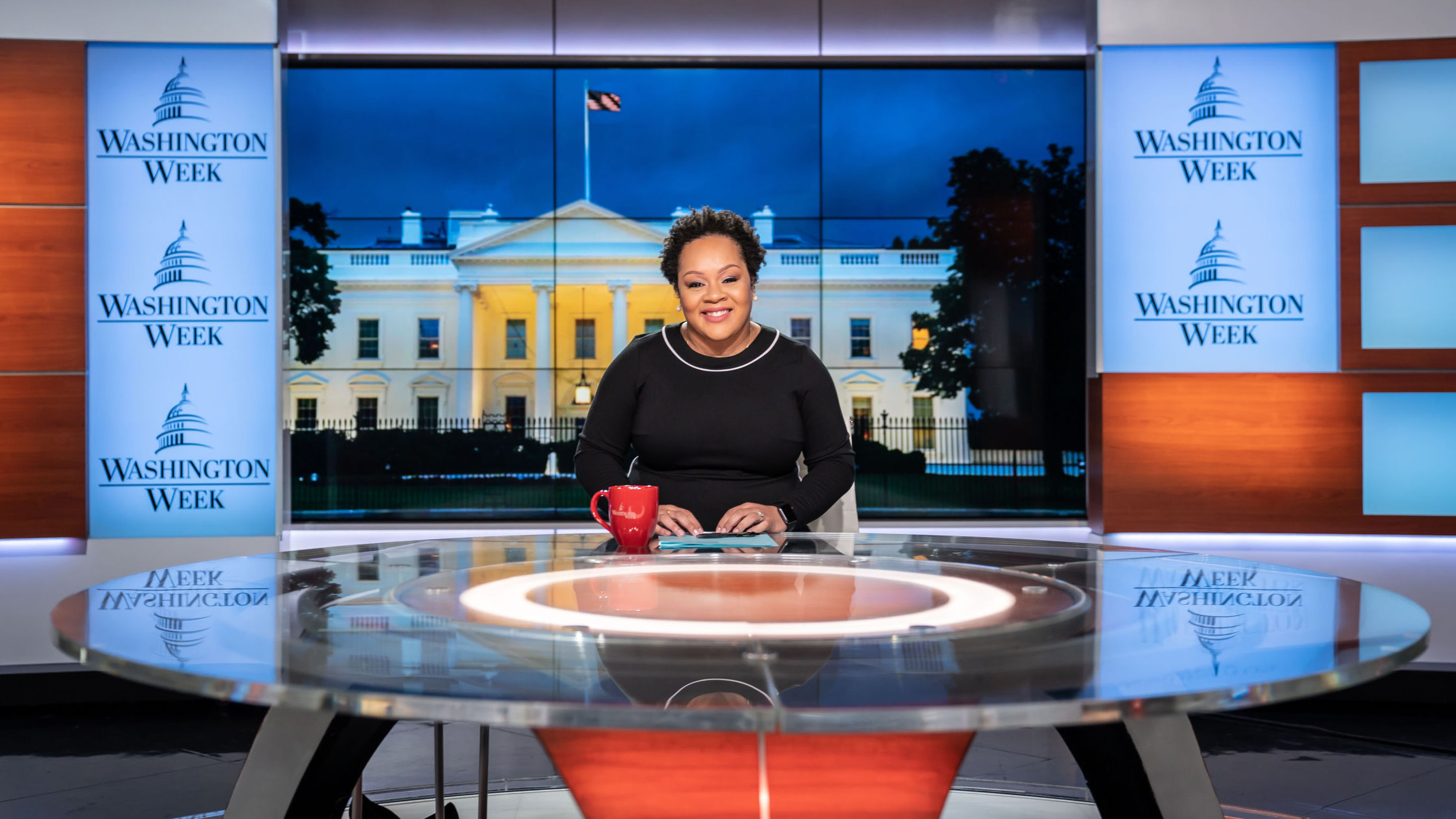 A black woman with short hair sits at glossy anchor desk in TV studio that pictures White House at night behind her. A red coffee cup sits near her right hand.