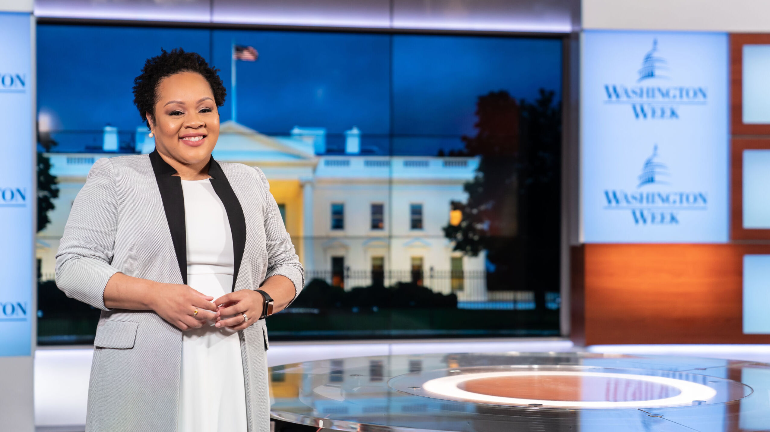 A Black woman with short hair wears a grey tailored long jacket over a white dress. She stands in the foreground of a tv set depicting the White House at night in background.