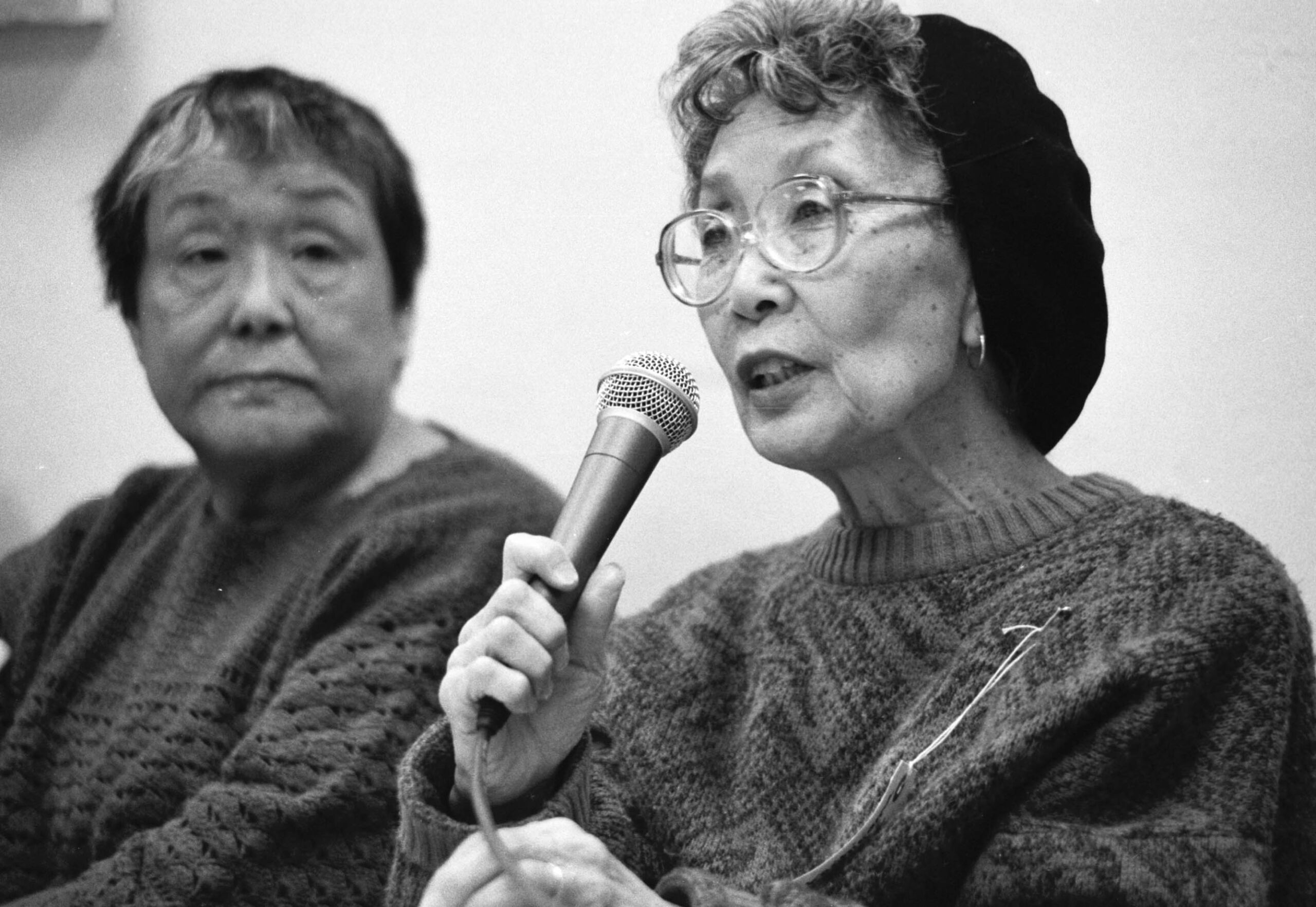 Black and white photo of older Asian woman with eyeglasse, hair tucked in a dark knit hat, sweater speaking into a microphone she holds. To her left, an older Asian woman with short hair and sweater looks at her.
