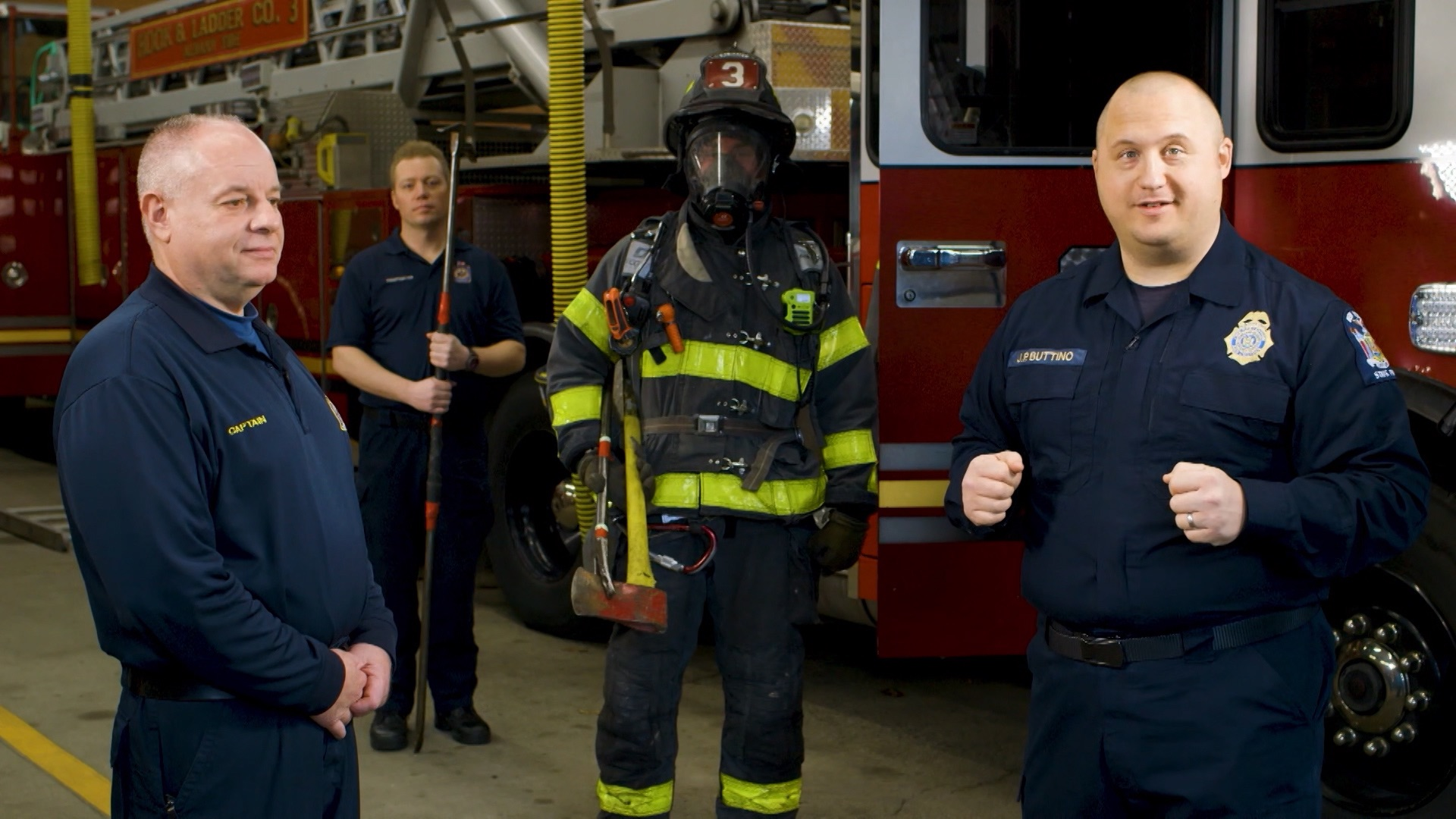 Four firefighters appear in different types of uniform in front of a firetruck.