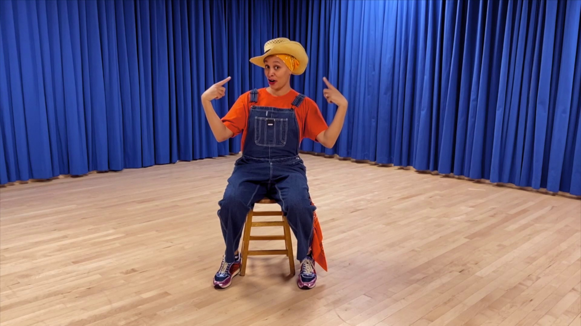 A woman wearing blue overalls and orange t-shirt and floppy hat sits on a chair in middle of dance floor. Behind her are bright blue stage curtains.