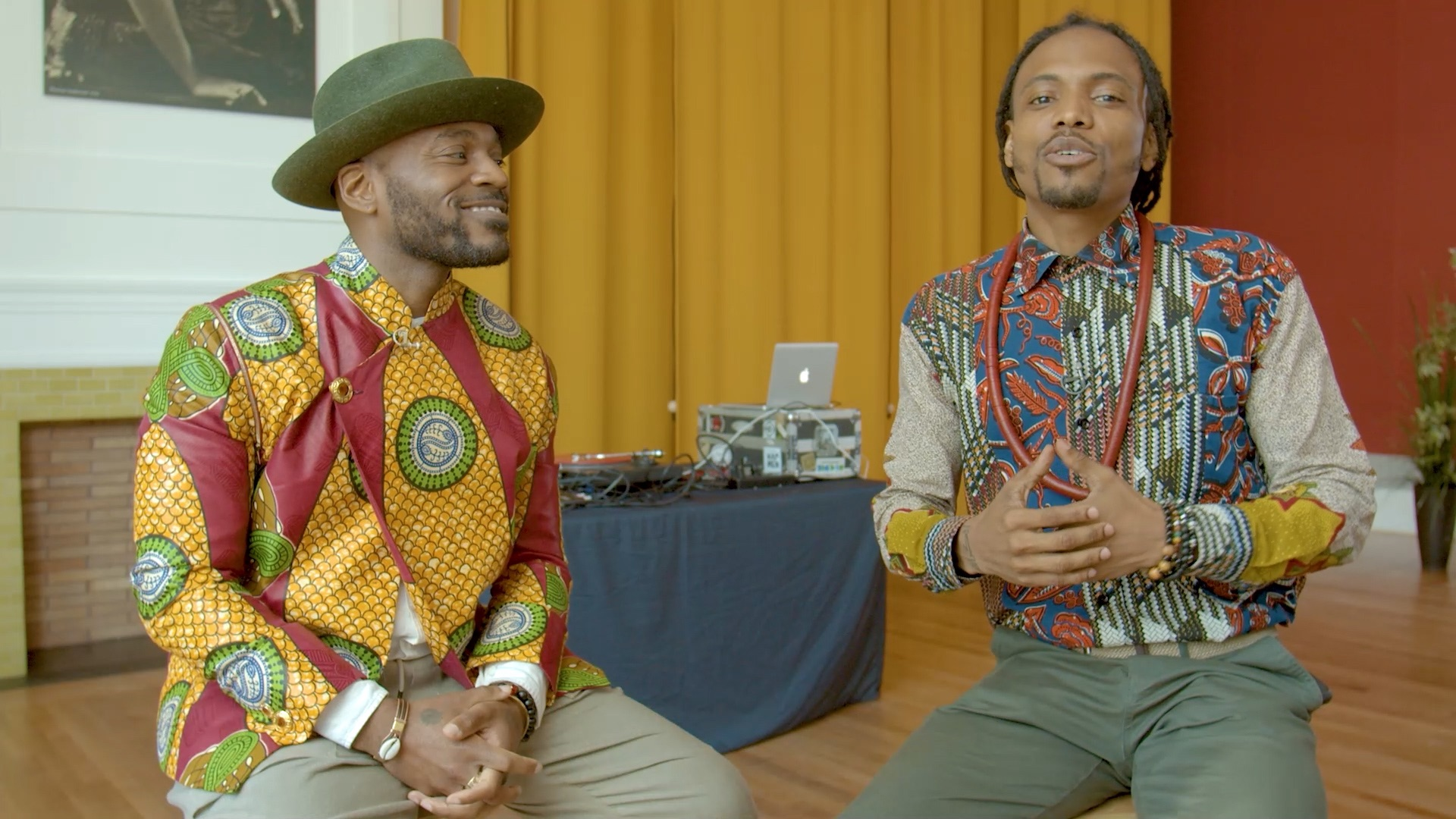 Two young black men sit on stools in a room and both wear colorful West African shirts. A curtain and DJ set up is visible in background