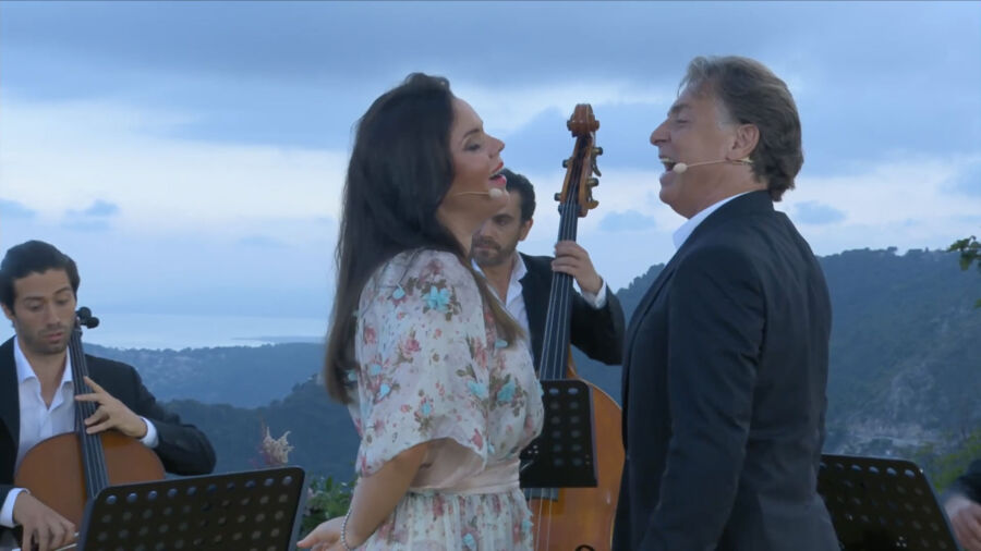 A woman in white flowered dress and long brown hair faces man in suit and they sing together. Around them are stringed instrument players and a vista overlooking a green landscape at dusk.